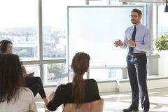 AffärsmanMaking Presentation To kollegor i regeringsställning Arkivbild