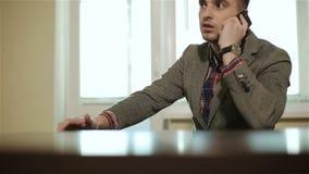 Affärsmanmannen i rutigt omslag talar på mobilt sammanträde på tabellen framme av fönstret arkivfilmer