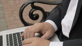 Affärsmanmaskinskrivning på en bärbar dator och sammanträde på en bänk i gatan stock video