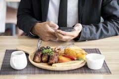 Affärsmannen är äta och genom att använda smartphonen arkivbild