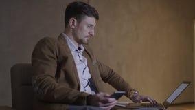 Affärsmannen är att använda som är båda hans mobil nad en bärbar datordator arkivfilmer