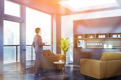 Affärsmannen är slö i regeringsställning med kaffemaskinen arkivfoto