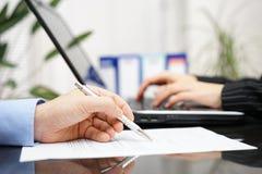 Affärsmannen är undersöker dokumentet, och kvinnan arbetar på bärbar dator c Arkivfoto