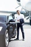 Affärsmannen öppnar bildörren arkivfoto