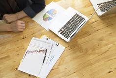 Affärsmannen analyserar data från diagram för affärsrapport Bästa sikt av det träfunktionsdugliga skrivbordet med labtop royaltyfri foto