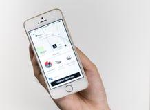 Affärsmannen använder den Uber applikationen på hans iPhone Arkivbilder