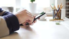Affärsmannen använder en smartphone i kontoret på arbetsplatsen arkivfilmer