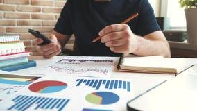 Affärsmannen använder en smartphone och att kontrollera den finansiella rapporten och diagram i kontoret på arbetsplatsen stock video