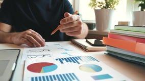 Affärsmannen använder en smartphone och att kontrollera den finansiella rapporten och diagram i kontoret på arbetsplatsen arkivfilmer