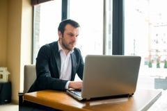 Affärsmannen använder hans dator i en restaurang Royaltyfri Bild