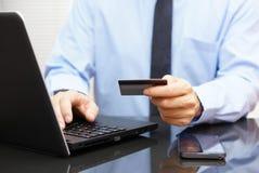 Affärsmannen använder kreditkorten för på linjen betalning på bärbara datorn Arkivfoto