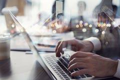 Affärsmannen arbetar i regeringsställning med bärbara datorn i förgrunden Begrepp av teamwork och partnerskap dubbel exponering royaltyfri fotografi