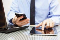 Affärsmannen arbetar på minnestavlan och använder den smarta telefonen Arkivfoton