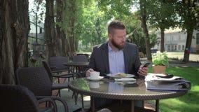 Affärsmannen avslutar påringning och att koppla av under lunch steadicamskott arkivfilmer