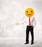 Affärsmannen bär den gula smileyframsidan Arkivbilder