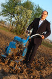 Affärsmannen bak en traktor. arkivfoto