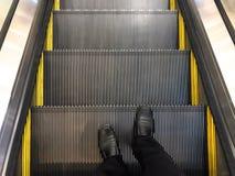 Affärsmannen bar svarta läderskor som står på rulltrappan Ner hissen arkivfoton