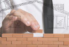 Affärsmannen bygger ett nytt hus royaltyfri bild