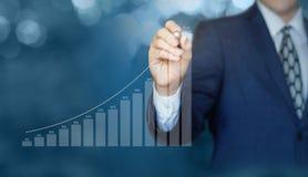 Affärsmannen drar en graf av statistik royaltyfri foto