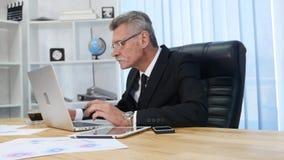 Affärsmannen dricker coffe, medan hålla ögonen på bärbar datorskärmen stock video