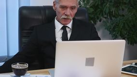 Affärsmannen dricker coffe, medan hålla ögonen på bärbar datorskärmen lager videofilmer