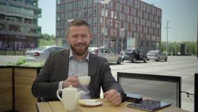 Affärsmannen dricker kaffe och ler för kameran, steadicam lager videofilmer