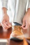 Affärsmannen eller brudgummen band ett skosnöre på hans bruna skor Fotografering för Bildbyråer