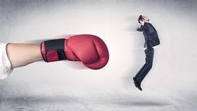 Affärsmannen får avfyrad av en enorm boxninghand royaltyfri fotografi