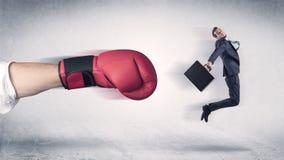 Affärsmannen får avfyrad av en enorm boxninghand arkivbild