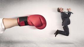 Affärsmannen får avfyrad av en enorm boxninghand royaltyfri bild