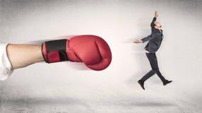 Affärsmannen får avfyrad av en enorm boxninghand royaltyfri foto
