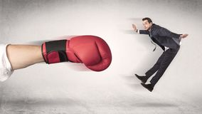 Affärsmannen får avfyrad av en enorm boxninghand arkivfoto