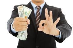 Affärsmannen fattar oss dollar med ok gest Arkivbild
