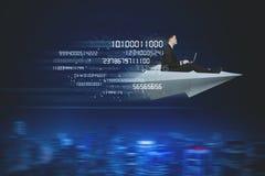 Affärsmannen flyger med den pappers- nivån och binär kod arkivfoton