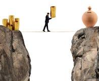 Affärsmannen flyttar en hög av mynt till en moneybox begrepp av sparande pengar för svårighet arkivbilder