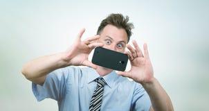 Affärsmannen fotograferar smartphonen Royaltyfri Bild