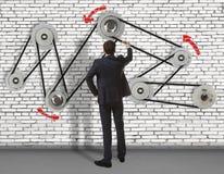 Affärsmannen framkallar mekanismen på väggen Arkivfoton