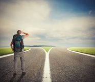 Affärsmannen framme av en crossway måste välja den högra vägen Arkivbild