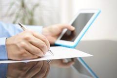 Affärsmannen fyller rapporten efter läs- anvisning på tabellen fotografering för bildbyråer