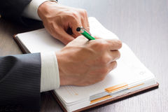 Affärsmannen gör anmärkningar till hans dagbok Arkivfoton