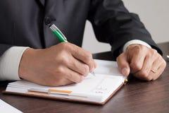 Affärsmannen gör anmärkningar till hans dagbok Arkivfoto