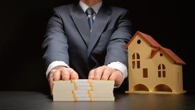 Affärsmannen ger en pengarbunt nära en husmodell på en tabell Fotografering för Bildbyråer