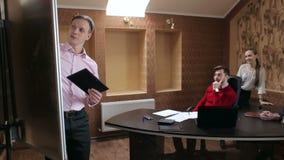 Affärsmannen ger en presentation för dina framstickande och kollegor stock video