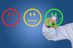 Affärsmannen ger en rösta för tjänste- kvalitet med en grön smiley arkivbilder