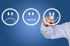 Affärsmannen ger en rösta för tjänste- kvalitet med en smiley Royaltyfri Foto