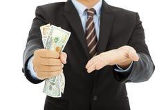 Affärsmannen griper hårt om oss dollar och gör en gest Royaltyfri Foto