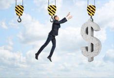 Affärsmannen hänger på kroken och når för stort dollartecken Arkivfoton