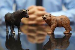 Affärsmannen håller ögonen på tjuren och björnen, begrepp av aktiemarknaden arkivfoto