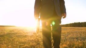 Affärsmannen i allvarlig dräkt med portföljen i hand promenerar vägen i afton i ilsken blick av inställningssolen bonde, och stock video