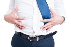 Affärsmannen i closeup rymmer hans mage på grund av bloating royaltyfri bild